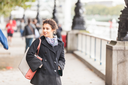thames: Young mixed race woman walking  in London on the Queens Walk next to Thames river. She is wearing a black coat and a scarf. Big Ben and Parliament on background. Tourism and lifestyle concepts.