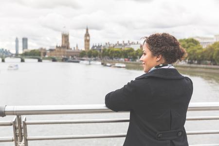 persone nere: La giovane donna di razza mista su un ponte a Londra. Lei indossa un cappotto nero e appoggiato alla ringhiera guardando fiume Tamigi e il Big Ben sullo sfondo. Turismo e stile di vita. Archivio Fotografico