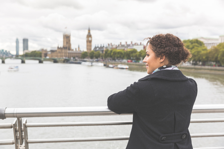 woman portrait: Young mixed race woman on a bridge in London. She is wearing a black coat and leaning on the railing while looking at Thames river and Big Ben on background. Tourism and lifestyle concepts.
