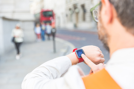 shot from behind: Male commuter in London looking at his smart watch. Shot from behind, focus on the finger tapping on the watch. Urban lifestyle and new technologies concepts.