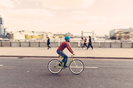 bicycles: Hipster man cycling on London bridge with Thames river and Tower Bridge on background. He is riding a fixed gear bike and wearing blue jeans and a red sweater. Panning technique.