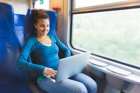 ferrocarril: Mujer joven que trabaja con el ordenador en el tren. Ella es de casi treinta años, sentado junto a la ventana y mirando la pantalla del ordenador. Los conceptos de viajes y estilo de vida. Foto de archivo