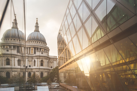 both sides: St Paul Cathedral in London and its reflection on a modern building facade at sunset.  The dome is in the middle of the image, and on both sides there are glass windows with its reflection. Stock Photo