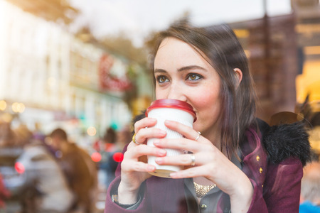 Beautiful young woman in a cafe holding a cuf of tea, seen through the window with buildings and lights reflections. She is looking away. Lifestyle concept.