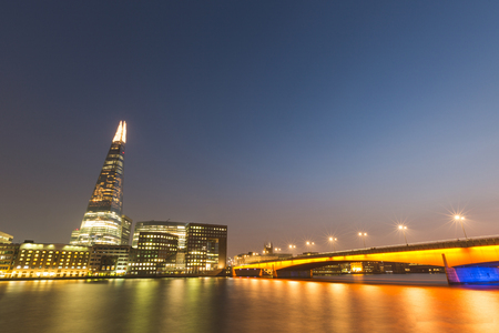 london bridge: London cityscape at night, long exposure. There is the Thames river on foreground, London bridge on the right and some modern buildings and skyscrapers on background.