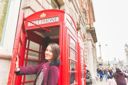 cabina telefonica: Mujer joven en Londres delante de una cabina de tel�fono rojo t�pico. Ella est� de pie en el costado, manteniendo la puerta con la mano, sonriendo y mirando a la c�mara. Turismo y estilo de vida concepto