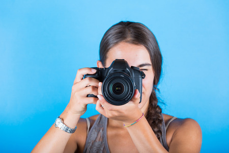picture person: Young woman taking pictures with a professional camera. She is looking inside the viewfinder, standing over a blue background. Head and shoulders view.
