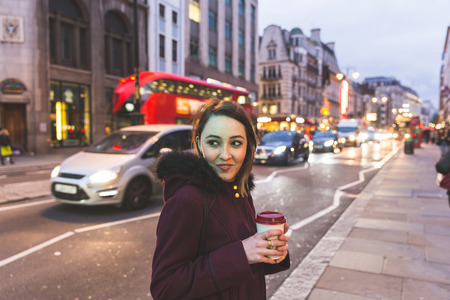 mid twenties: Young woman in London standing by a busy road at night. She is on her mid twenties, holding a cup of coffee or tea and looking at camera. Her face is illuminated by traffic light.