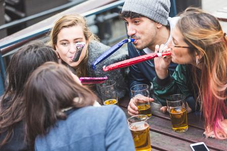 jovenes tomando alcohol: Cuatro mujeres y un hombre est�n jugando algunos trompetas de papel. Ellos son al aire libre en beber cerveza pub. Est�n teniendo una peque�a fiesta y todo el mundo es feliz. estilo de vida y felicidad conceptos. Foto de archivo