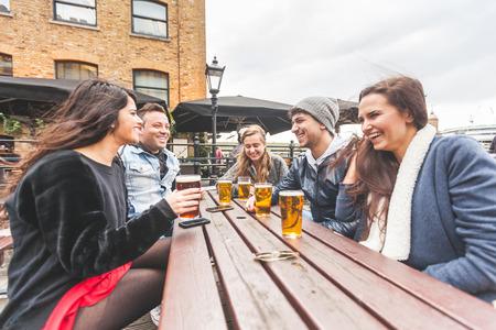 jovenes tomando alcohol: Grupo de amigos disfrutando de una cerveza en el pub en Londres, tostar y riendo. Est�n sentados fuera en una mesa de madera, vestido con ropa de invierno. Conceptos de amistad y de estilo de vida.