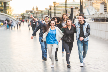 Multiracial group of friends enjoying their time in London. They are four women and two men in their twenties, they are walking, laughing and having fun together. Friendship and lifestyle concepts.