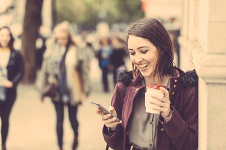 Jonge vrouw in Londen stond bij de stoep, met een kopje thee en typen op haar slimme telefoon. Het is een bewolkte winter dag, en er zijn vele wazig mensen op achtergrond. Stockfoto