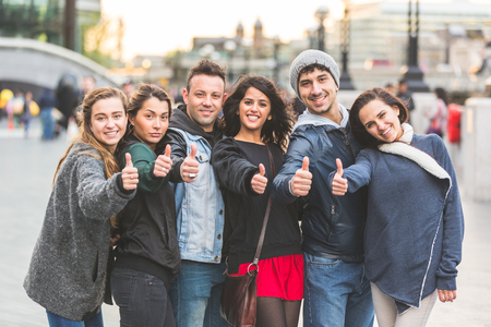 Successful group of friends showing thumbs upin London. They are four women and two men in their twenties, they are standing in a row, all very close by each other. Friendship and lifestyle concepts.