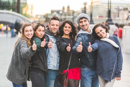Succesvolle groep van vrienden tonen duimen UPIN Londen. Ze zijn vier vrouwen en twee mannen van in de twintig, zijn ze zich in een rij, allemaal heel dicht bij elkaar. Vriendschap en lifestyle concepten.