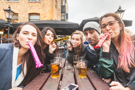 pubs: Four girls and one boy are playing some paper trumpets. They are outdoor at pub, looking all together at camera. They are having a small party and everybody is happy.