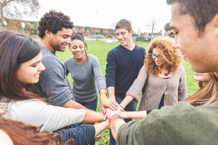 trabajo en equipo: Grupo multirracial de amigos con las manos en la pila, fuerte concepto de trabajo en equipo y la cooperación, también se refiere a la inmigración y la amistad.
