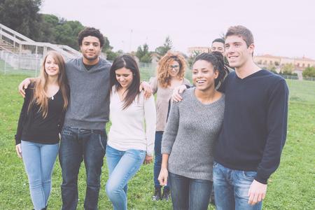 jovenes estudiantes: Grupo multiétnico de amigos en el parque a pie y disfrutar del tiempo juntos. Grupo de la raza mezclada con la gente caucásica, negros y asiáticos. Conceptos Amistad, estilo de vida, de inmigración.