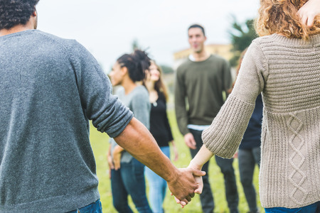 Multiethnic group of friends holding hands in a circle. The focus is on two hands with many other persons on background. Teamwork, integration, community, friendship concepts