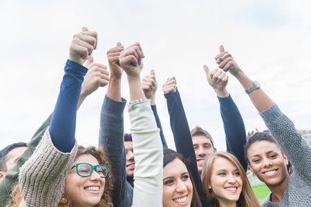 trabajo en equipo: Grupo multiétnico de amigos con los pulgares para arriba. Ellos están en el parque, de pie al lado del otro, con las caras felices y sonrientes. Éxito del trabajo en equipo y conceptos.