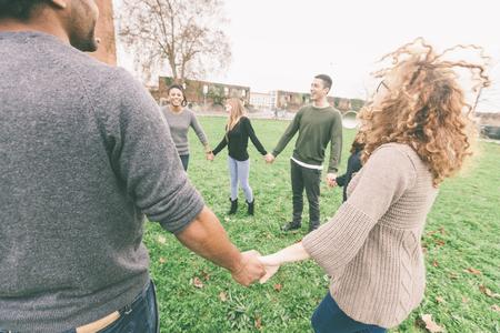 Multi-etnische groep van vrienden hand in hand in een cirkel. De focus ligt op twee handen met vele andere personen op de achtergrond. Teamwork, integratie, gemeenschap, vriendschap concepten Stockfoto
