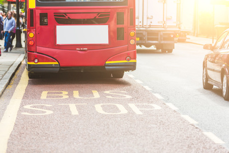 lanes: Red double-decker bus at bus stop in London. View from back, with focus on BUS writing on the road. on the left there are some persons and on the right some vehicles. Urban transport concept. Stock Photo
