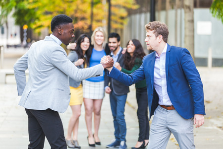 arm: Two business men compete in arm wrestling with some colleagues inciting them. They are a black man and a caucasian one wearing smart casual clothes. Challenge and competition concepts.