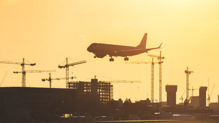 city of london: Airplane landing at sunset at London City airport. Silhouette shot with buildings and cranes on background. The plane has gear down already Stock Photo