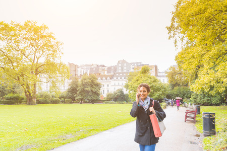 late twenties: Young woman talking on the phone at park in London. She is a beautiful mixed race woman on her late twenties, the weather is cloudy and cold. Lifestyle and communications concepts.