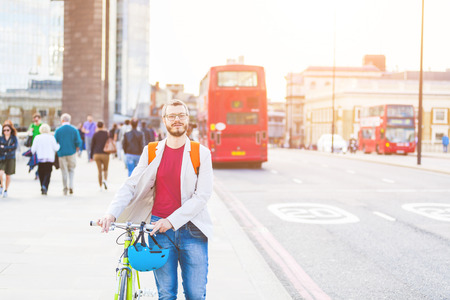 street people: Hipster man walking on London bridge and holding his fixed gear bike. He is walking on the sidewalk, and there are some people and red buses on background. Lifestyle and transportation concepts. Stock Photo