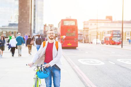 personas en la calle: Hombre inconformista caminando sobre el puente de Londres y la celebración de su bicicleta artes fijos. Él está caminando en la acera, y hay algunas personas y autobuses rojos en el fondo. Estilo de vida y transporte conceptos. Foto de archivo