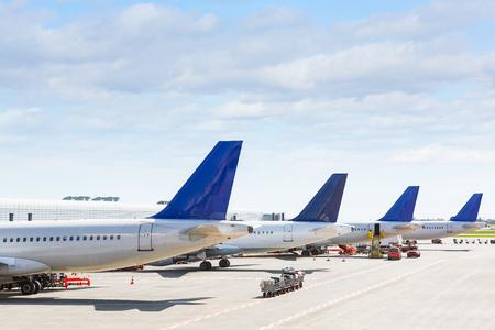 탑승 작업 중에 공항에서 일부 비행기의 꼬리. 그들은 푸른 하늘이 맑은 날에 네 개의 평면이다. 여행 및 교통 개념. 스톡 콘텐츠