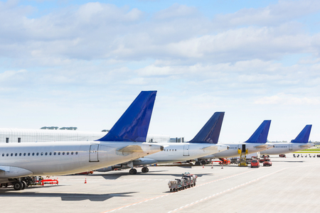 airplane: Tails of some airplanes at airport during boarding operations. They are four planes on a sunny day, with a blue sky. Travel and transportation concepts.