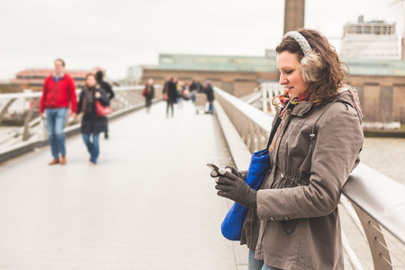 warm clothes: Beautiful woman typing on smart phone in London. She is leaning on the railing of a bridge, wearing warm clothes on a cold winter day. Travel, lifestyle and technology concepts.