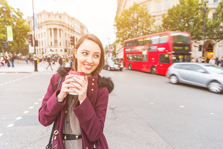 autumn young: Woman in London standing by a busy road holding coffee. She is on her mid twenties and looking away from camera. Blurred traffic on background. Travel and lifestyle concepts.