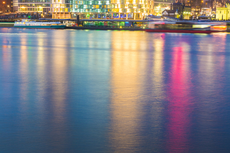 reflection: Colorful reflections on Thames river in London. Picture taken in the night with lights of buildings and skyscrapers reflecting into the water. Background and abstract.