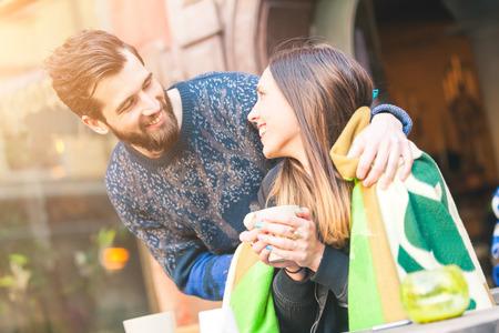 donna innamorata: Coppia giovane pantaloni a vita bassa in un caffè a Stoccolma. Si mette una coperta sulle spalle, è in possesso di una tazza di tè o di caffè caldo. Sono alla ricerca a vicenda sorridente. Amore o di amicizia concetti.