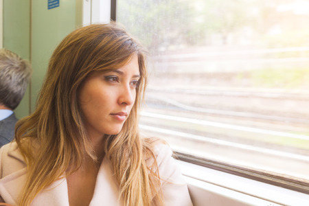 young add: Beautiful young woman looking out of train window. She is on her mid twenties, mixed race face, she seems to be pensive and sad. There is a free space on right to add some text. Travel concept
