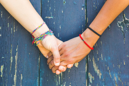 Two women holding hands with a wooden background. One is caucasian, the other is black. Multicultural, homosexual love and friendship concepts. Stockfoto