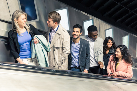 smiling businessman: Group of people on the escalator. They are a mixed group of persons, they could be friends or just strangers. Urban lifestyle and transportation concepts.