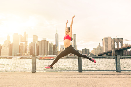 PRETTY WOMEN: Asian young woman jumping with New York skyline on background. She is on her early twenties, half Japanese and half Chinese, wearing fitness clothes. Success and healthy lifestyle concepts. Stock Photo