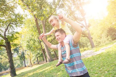 niños jugando en el parque: Padre e hija jugando en el parque en Nueva York. El hombre está llevando a la niña en sus hombros que llevan a cabo las manos. Ellos están buscando fuera de la cámara. Verano, la familia y los conceptos de estilo de vida