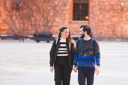 mujer alegre: Pareja joven inconformista caminar en Estocolmo con y antigua muralla en el fondo. Ellos son la celebraci�n de las manos y mirando mutuamente sonriendo. El amor, la moda y los conceptos de viaje. Foto de archivo