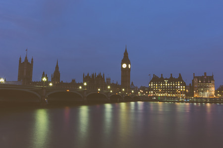 noire: Big Ben and Parliament building at dawn in London with Westminster bridge and Thames river in foreground. Dark vintage noire edit. Stock Photo