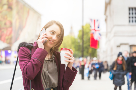 femmes souriantes: Young woman in London standing by the sidewalk, holding a cup of tea and talking on the phone. It is a cloudy winter day, and there are many blurred persons on background. Banque d'images
