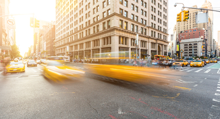 cities: Busy road intersection in Manhattan, New York, at sunset. There are some blurred yellow cabs on foreground, and buildings, people and cars on background. Long exposure shot. Travel and city life. Stock Photo