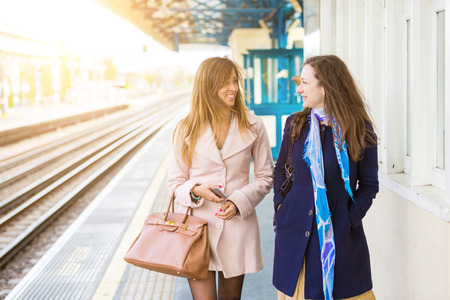 railway transportation: Two beautiful women walking along platform at train station. They are happy, smiling and looking each other. Autumn or winter setting, they are both wearing a coat. Travel and lifestyle concepts.