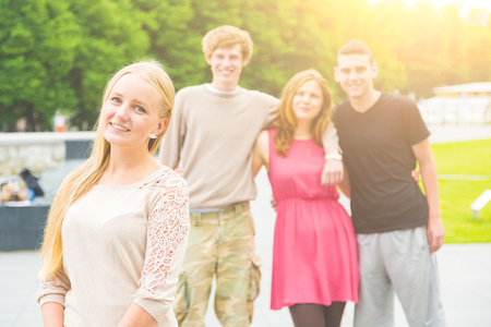 early twenties: Portrait of a blonde young woman with a small group of friends on background. She is in her early twenties, smiling and looking at camera. Multiethnic group. Friendship and lifestyle concepts.