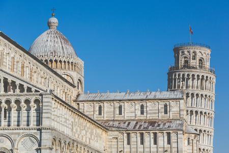 italian architecture: Famous leaning tower and Cathedral in Pisa, Italy. Close up view of these two famous Italian buildings, with a blue sky on background. Travel and architecture concepts. Vintage edit.
