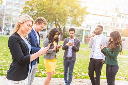 Multi-etnische groep van jonge mensen openlucht kijken naar hun eigen smartphones. Ze zijn zes personen, drie mannen en drie vrouwen, allen dragen smart casual kleding. Technologie en sociale media verslaving.