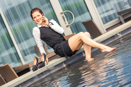 Young businesswoman having fun next to the swimming pool. She is in her mid thirties, wearing formal clothes, talking on the phone and looking at camera. Business concept.